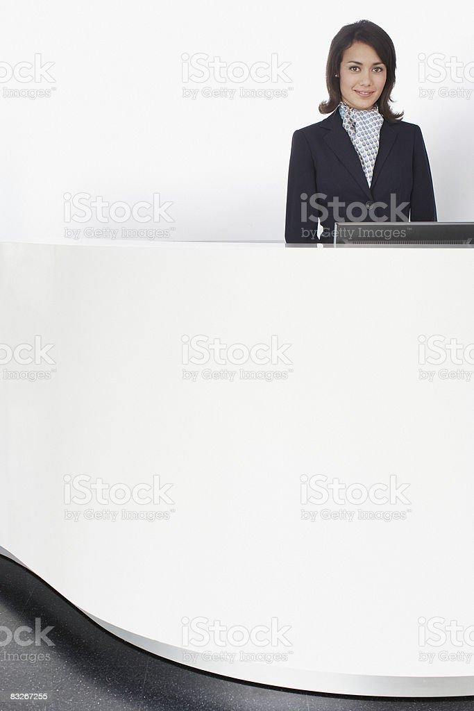 Businesswoman standing at reception desk royaltyfri bildbanksbilder