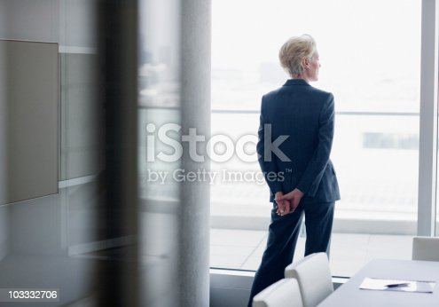 istock Businesswoman standing at window in office 103332706