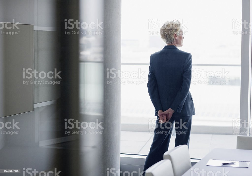 Businesswoman standing at window in office stock photo
