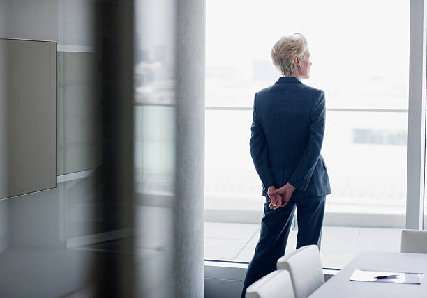 businesswoman standing at window in office - zelfreflectie stockfoto's en -beelden