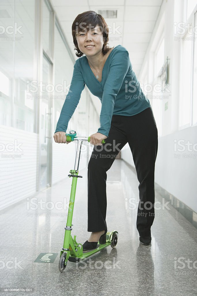 Businesswoman standing in corridor with push scooter, smiling, portrait royalty-free 스톡 사진