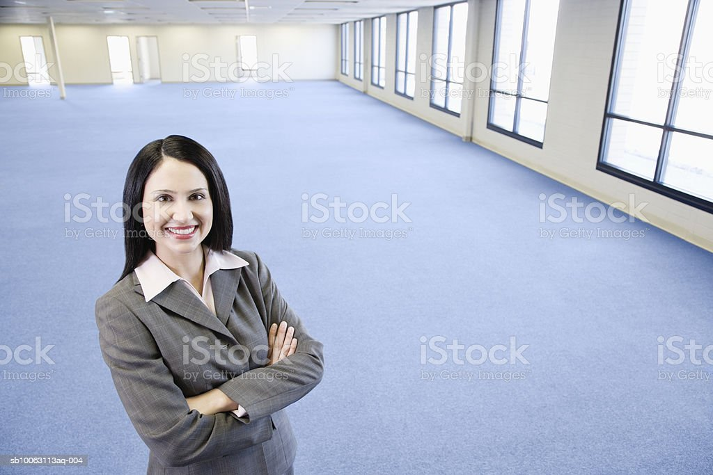 Businesswoman standing in empty office with arms crossed, smiling, portrait foto de stock libre de derechos