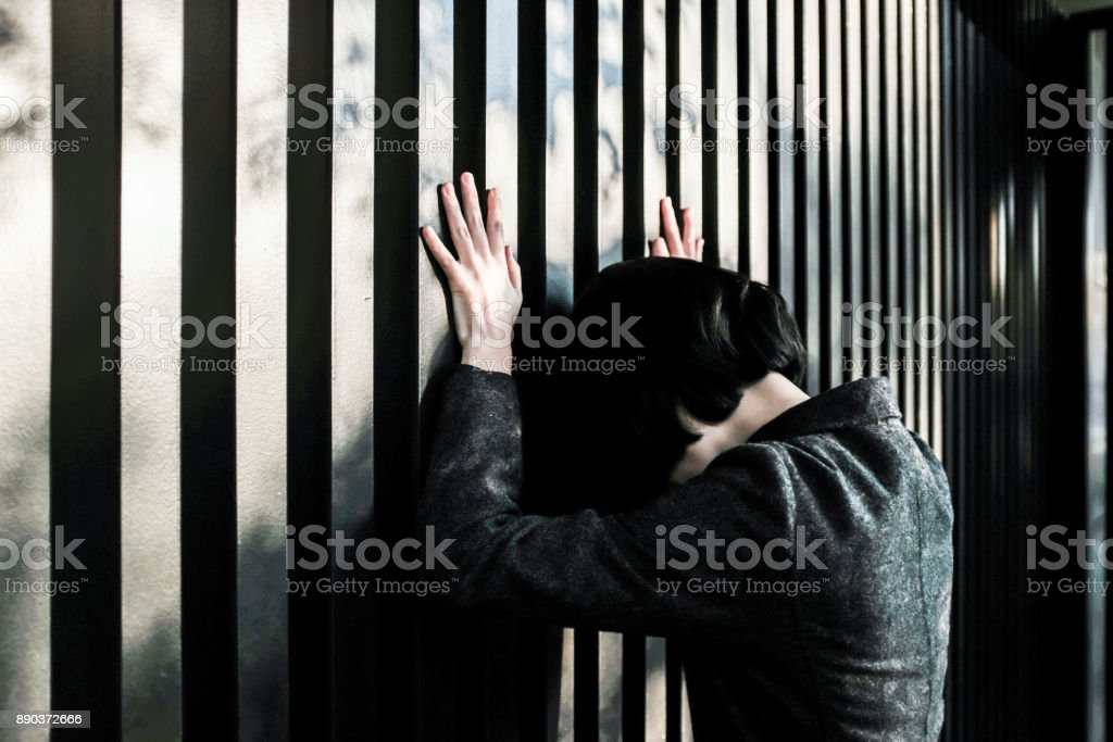 Businesswoman standing in front of a fence stock photo