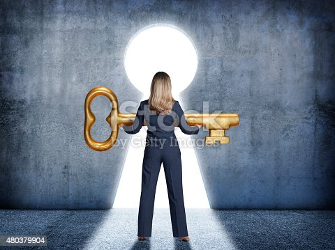 A businesswoman stands in front of a large keyhole holding a large golden key.  The businesswoman is standing with her back to the camera as the light from outside casts a strong shadow.