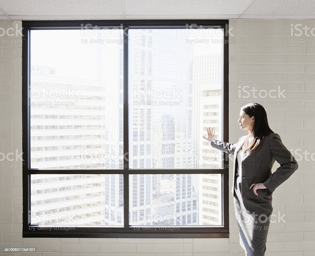 Businesswoman standing in front of window, hand on hip foto de stock libre de derechos