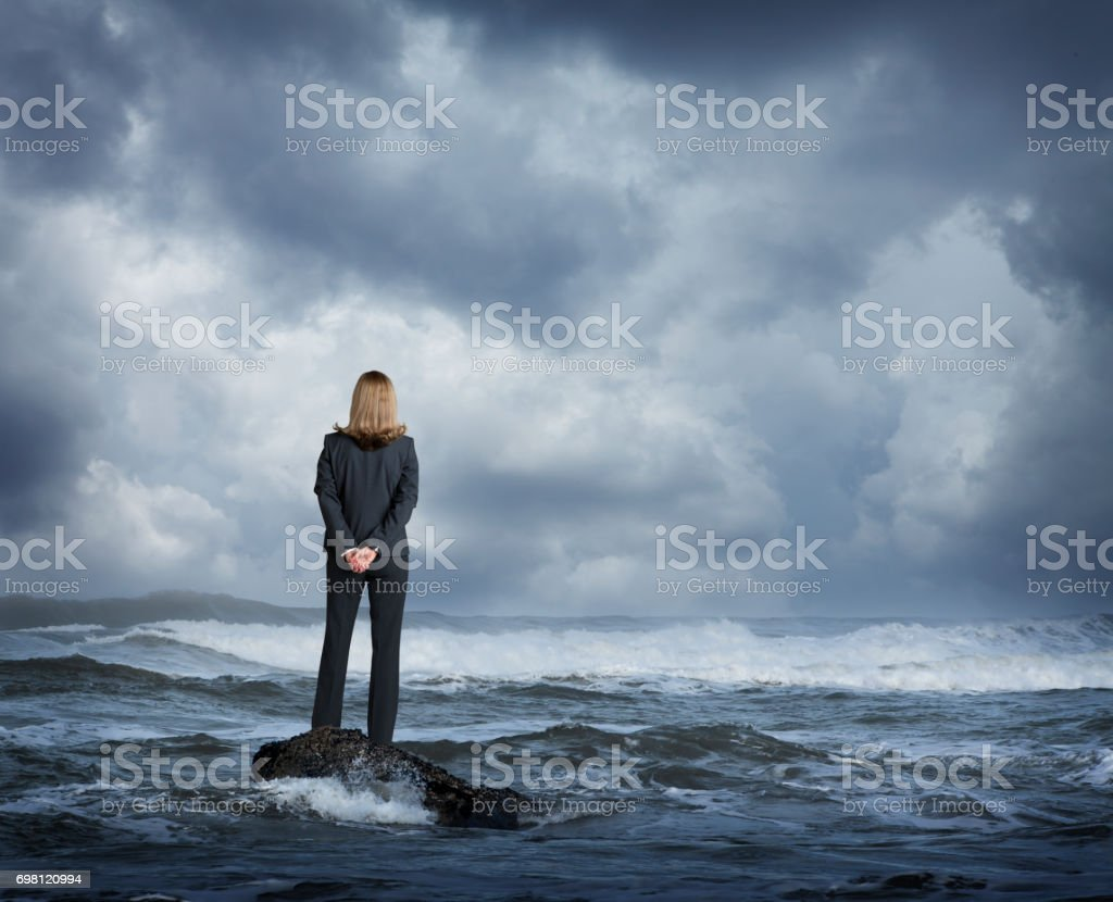 Businesswoman Standing In Rough Ocean Surf stock photo