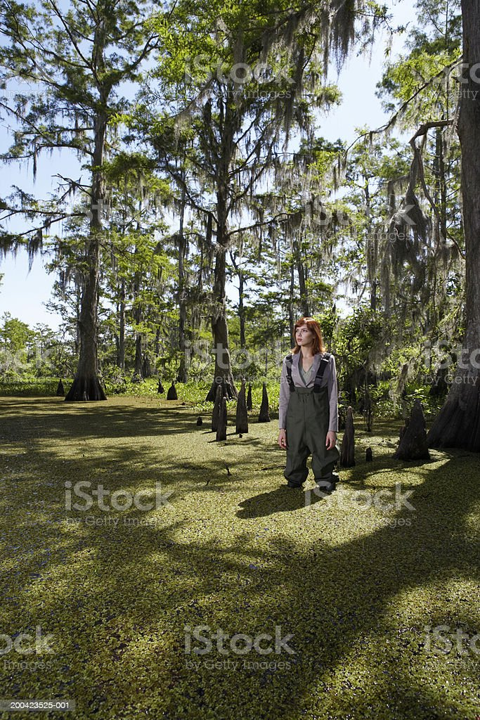 Businesswoman standing in swamp with hip waders royalty-free stock photo
