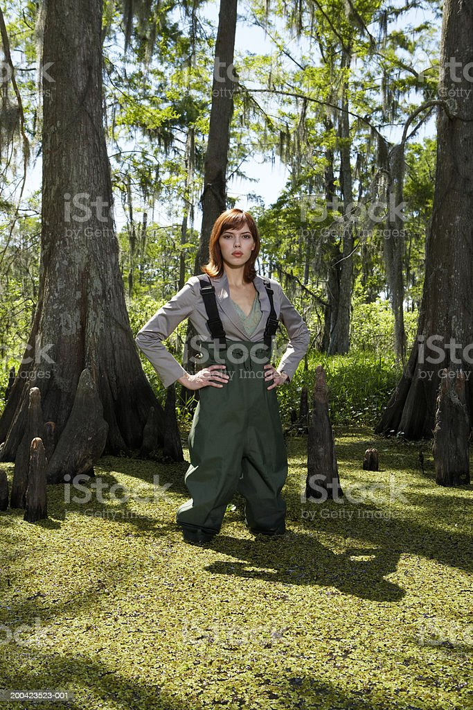 Businesswoman standing in swamp with hip waders, portrait royalty-free stock photo