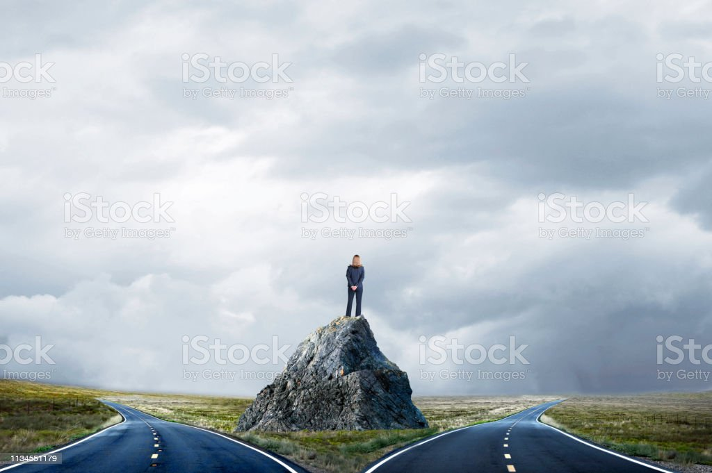 Businesswoman Standing On Large Rock Looking At Fork In The Road stock photo