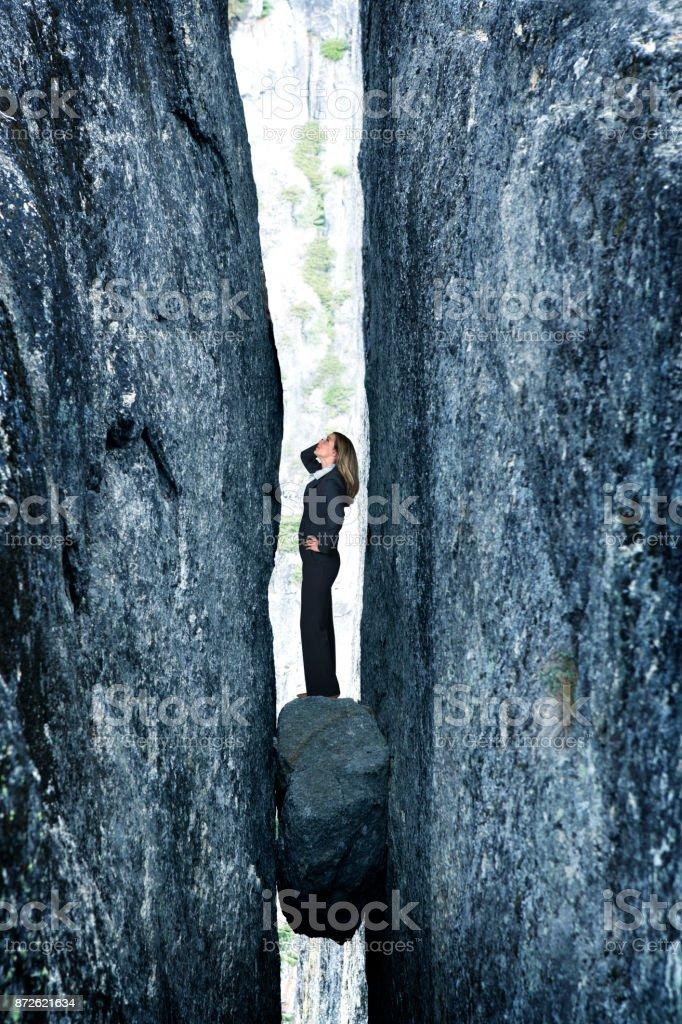 Businesswoman Standing On Rock Stuck In Deep Crevasse stock photo