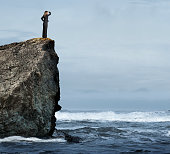 A businesswoman places her hand to her brow as she stands high on a rocky cliff and looks out toward stormy seas below her.