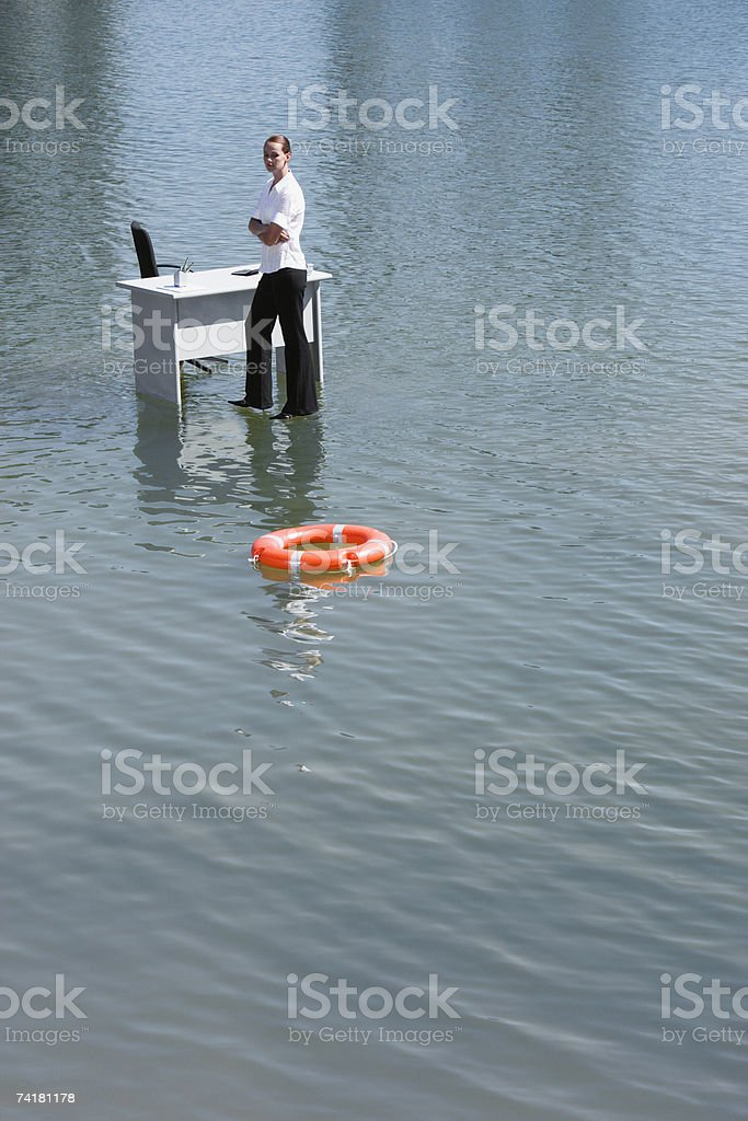 Businesswoman standing on water with floating device royalty-free stock photo