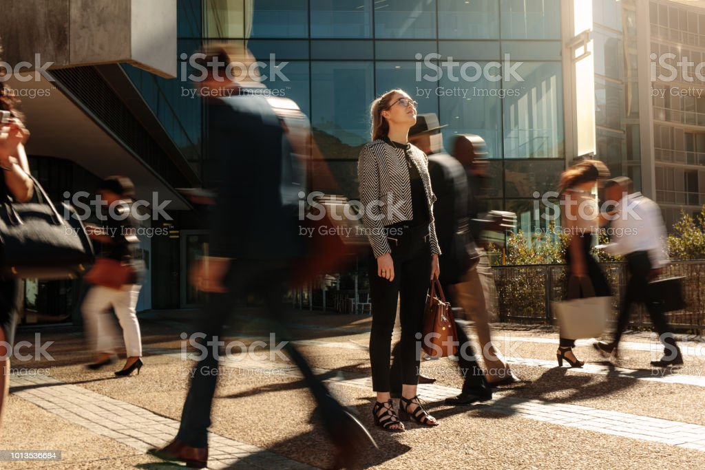 Businesswoman standing still on a busy street stock photo