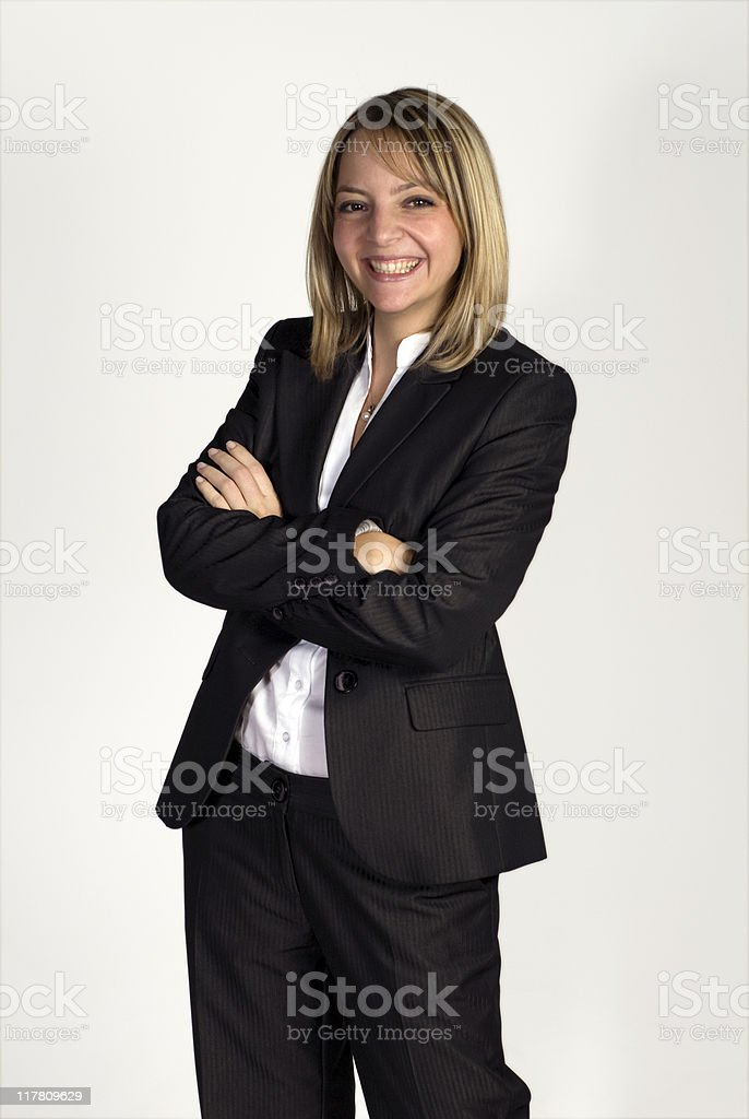 Businesswoman standing with arms crossed against white background, smiling, Turkey royalty-free stock photo