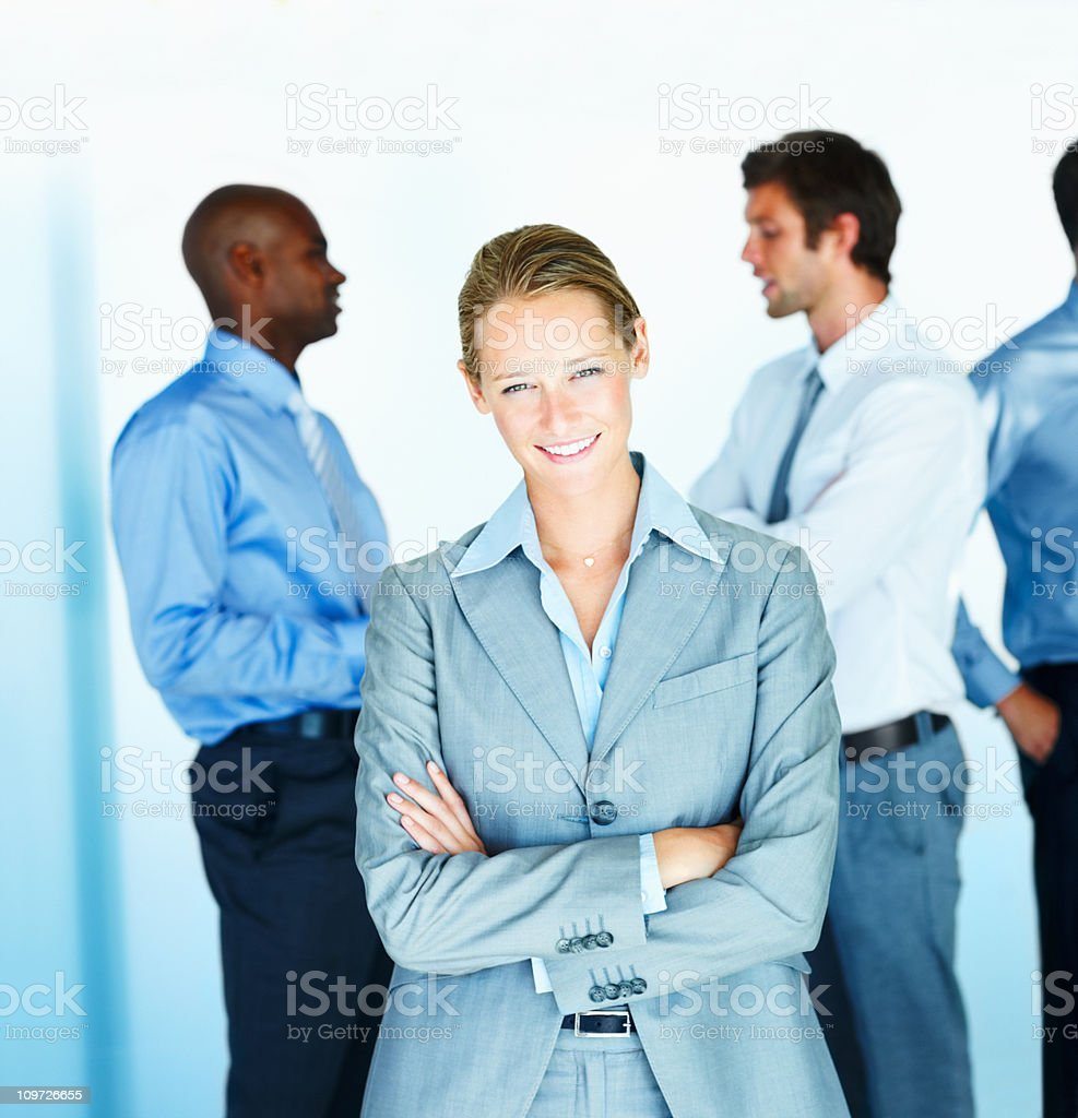 Businesswoman standing with colleagues in background royalty-free stock photo