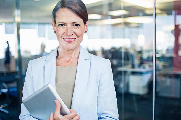 femme d'affaires debout avec tablette numérique - directrice photos et images de collection
