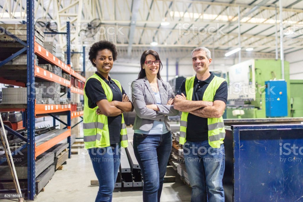 Businesswoman standing with warehouse workers in factory stock photo