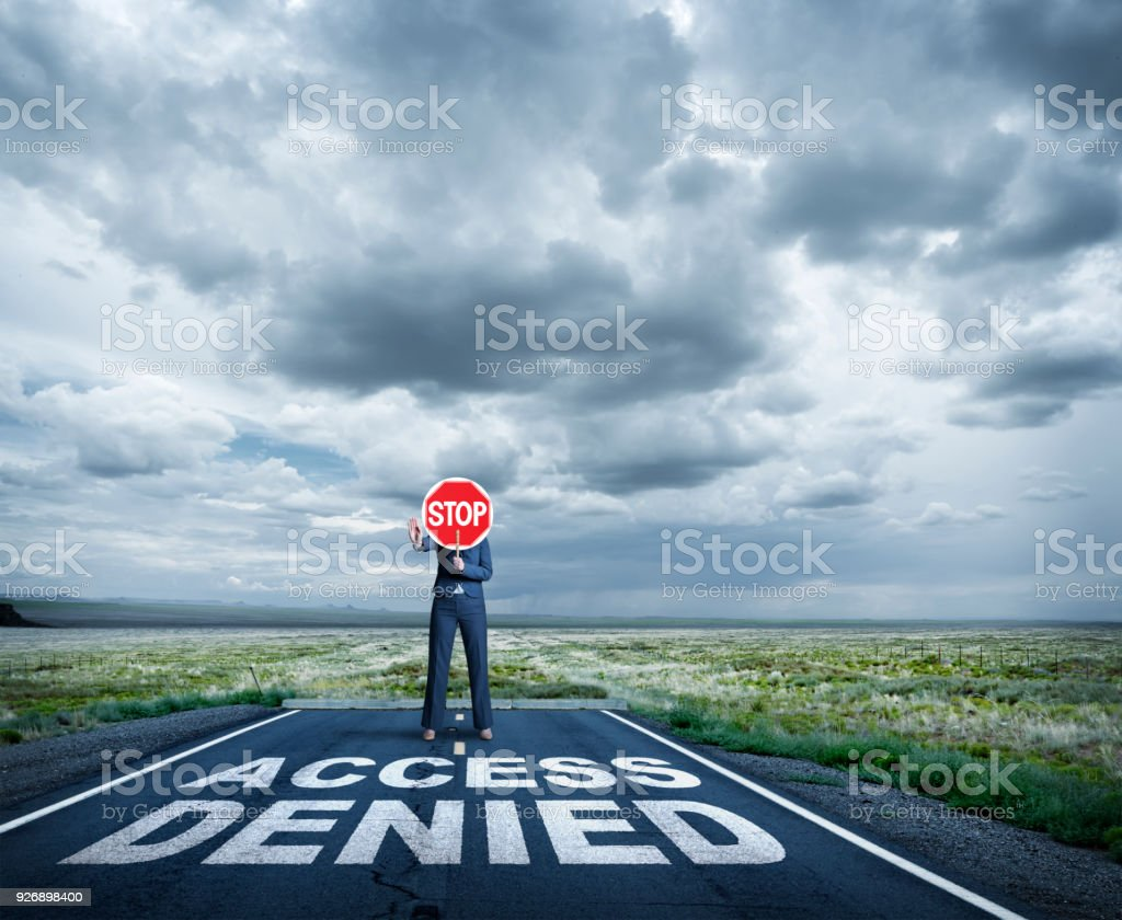 Businesswoman Stands At End Of Road Holding Stop Sign stock photo
