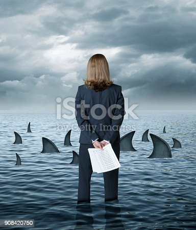 A rear view of a businesswoman standing knee deep in shallow water as she holds some paperwork behind her back and looks out towards sharks circling in the water in front of her.