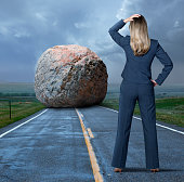 A rear view of a businesswoman standing on a long rural road as she places her hand on her head in disbelief and looks at a huge boulder that blocks her path.
