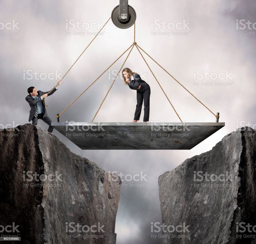 Businesswoman Stands On Bridge As Businessman Hoists It Into Place stock photo