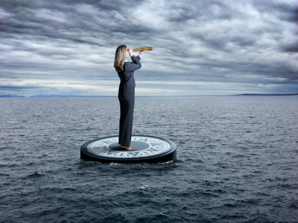 Businesswoman Stands On Compass Looking Through Spyglass In Stormy Sea stock photo