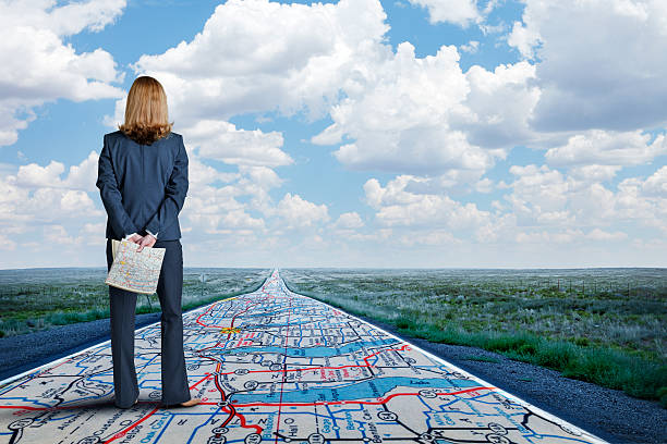 businesswoman stands on long road with road map painted on it - road map stock photos and pictures
