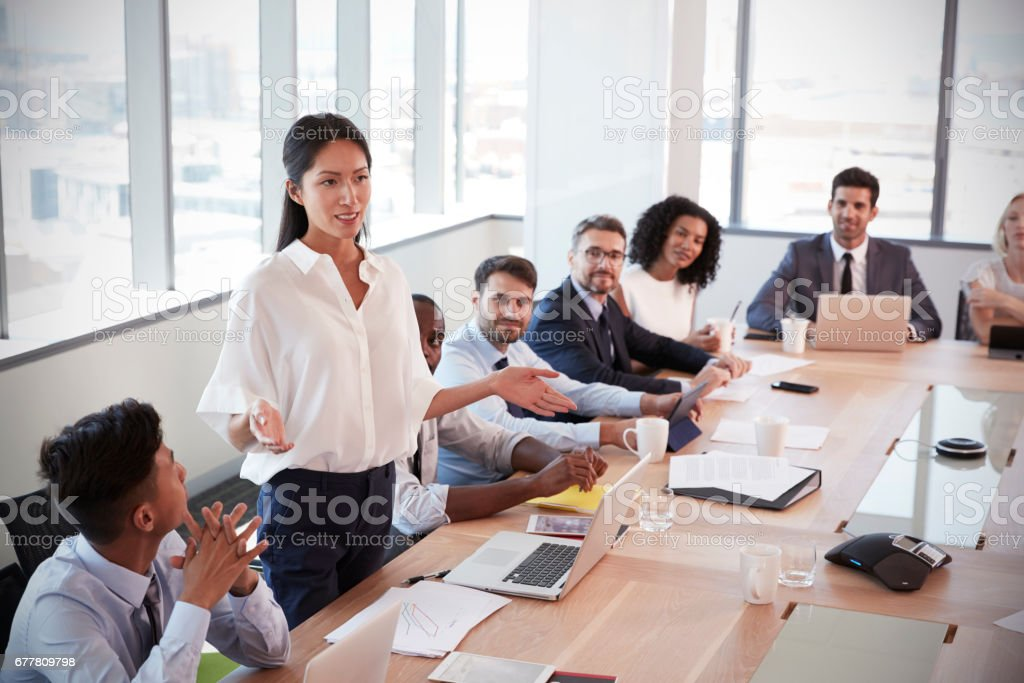 Businesswoman Stands To Address Meeting Around Board Table Businesswoman Stands To Address Meeting Around Board Table Leadership Stock Photo