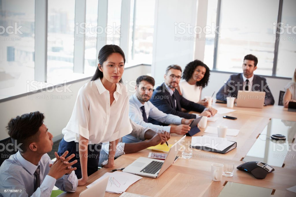 Businesswoman Stands To Address Meeting Around Board Table royalty-free stock photo