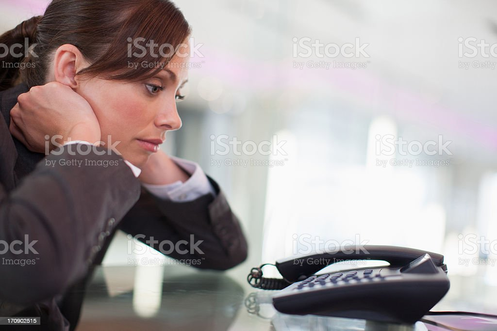 Businesswoman staring at telephone waiting for it to ring stock photo