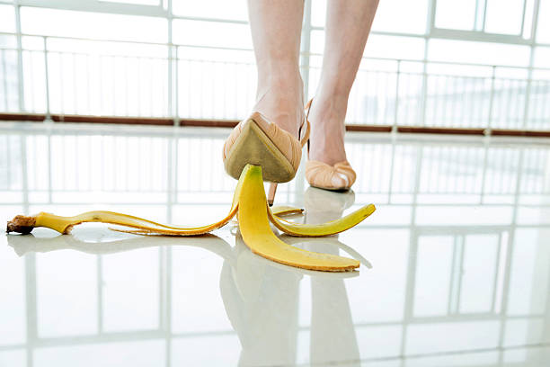 Businesswoman stepping on banana skin Businesswoman stepping on banana skin in office building hall. banana peel stock pictures, royalty-free photos & images