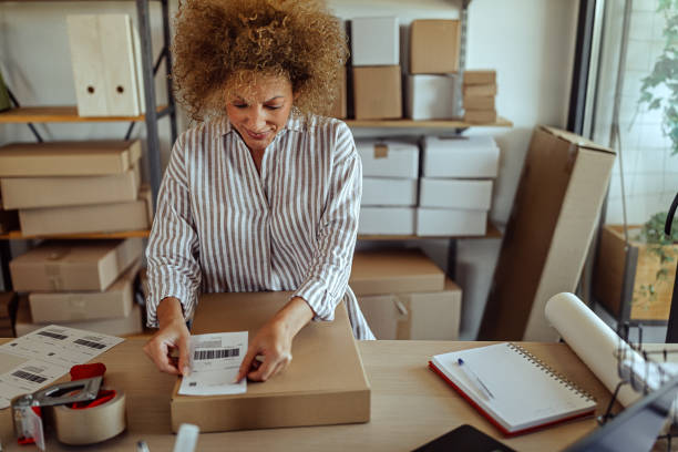 Businesswoman sticking bar code label on delivery package stock photo