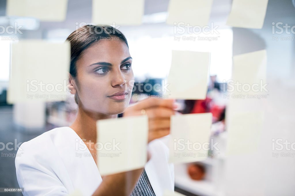 Businesswoman sticking notes on to window, business planning stock photo