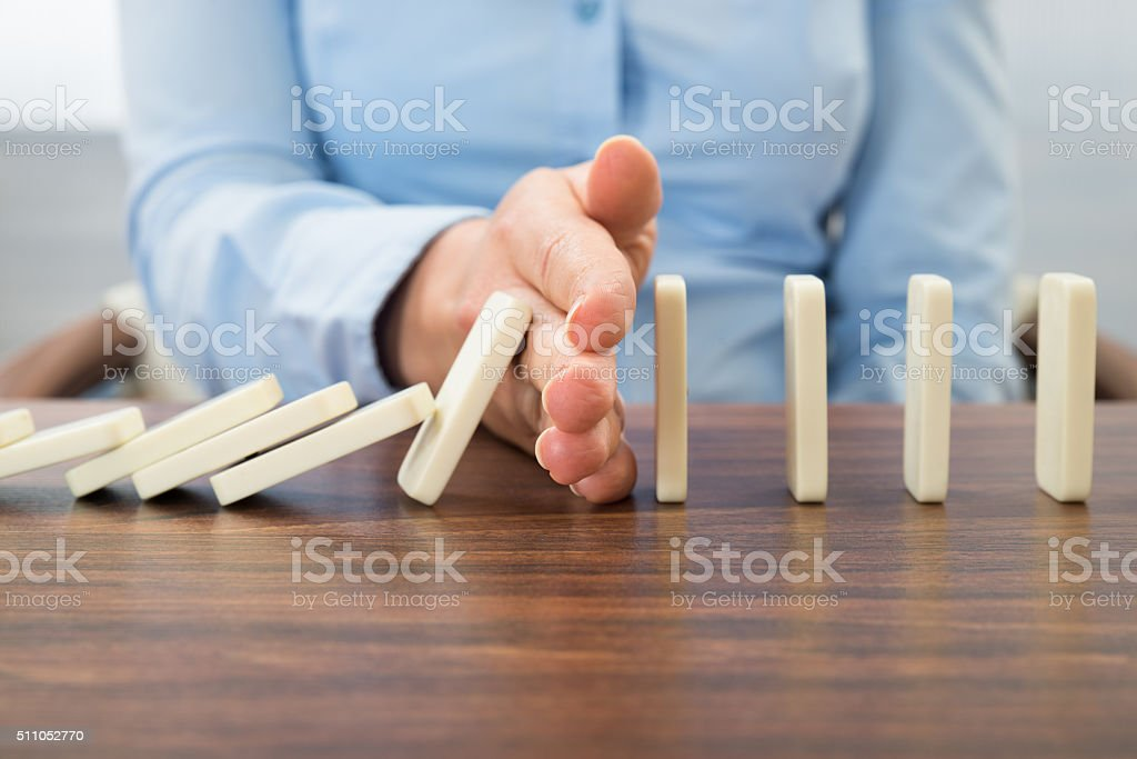 Businesswoman Stopping The Effect Of Domino stock photo