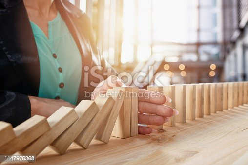 istock Businesswoman stops a chain fall like domino game. Concept of preventing crisis and failure in business 1147976368