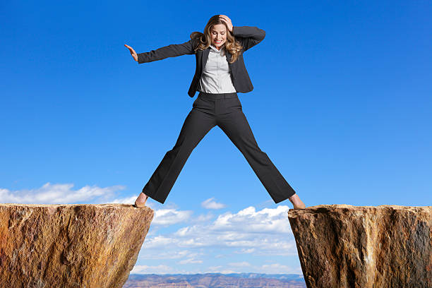 Businesswoman straddling the divide created by two cliffs stock photo