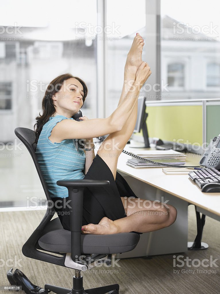 Businesswoman stretching at desk stock photo
