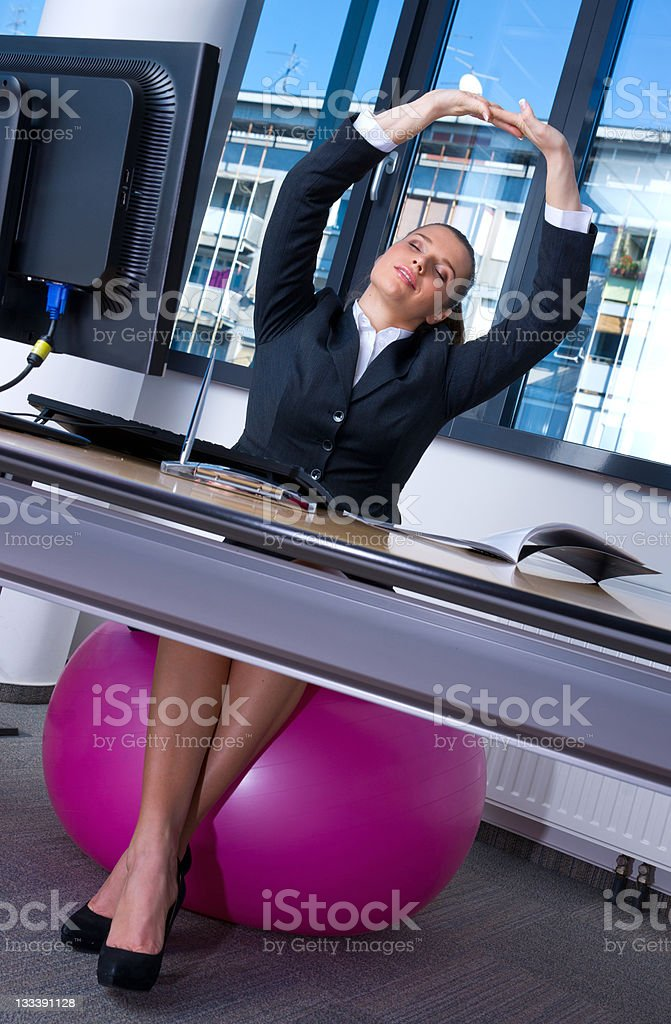 Businesswoman stretching body on pink Swiss ball in office royalty-free stock photo