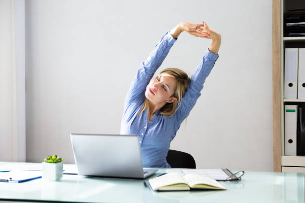 businesswoman stretching her arms - sitting stock pictures, royalty-free photos & images