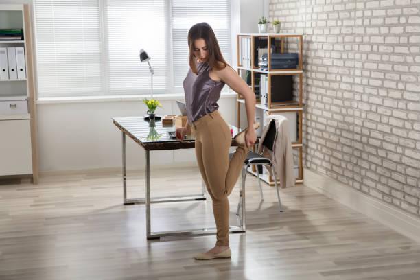 geschäftsfrau dehnen ihr bein im büro - yoga fürs büro stock-fotos und bilder
