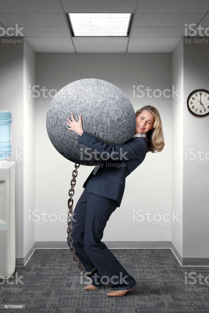 Businesswoman Struggles To Carry A Large Ball And Chain In Her Office stock photo
