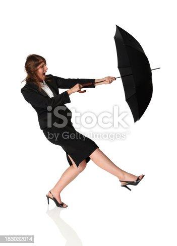 istock Businesswoman struggling with an umbrella 183032014