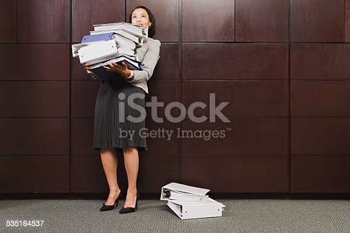1067846662 istock photo Businesswoman struggling with heavy files 535164537