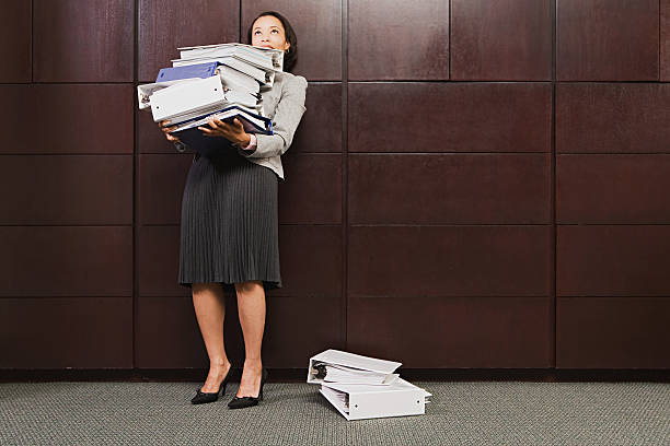 Businesswoman struggling with heavy files stock photo