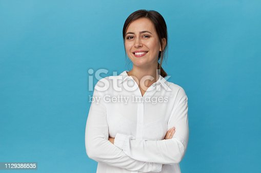 Amazing and cheerful smiling brunette with crossed arms in white shirt studio shot, isolated on blue