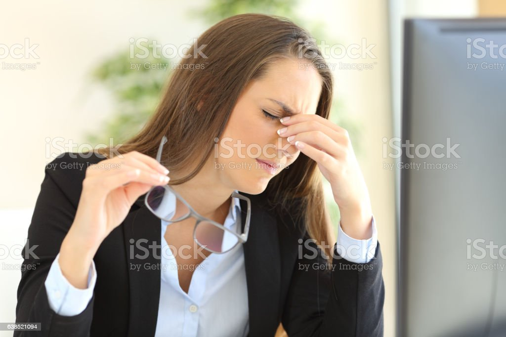 Businesswoman suffering eyestrain at office stock photo