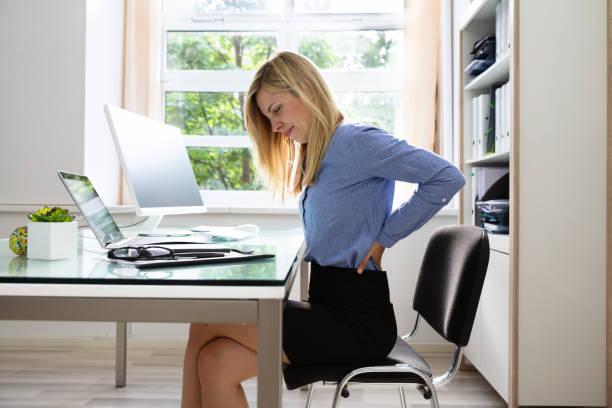 geschäftsfrau, die unter rückenschmerzen - rückenschmerzen beim sitzen stock-fotos und bilder