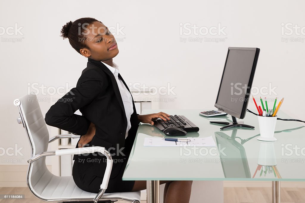Businesswoman Suffering From Backache In Office stock photo