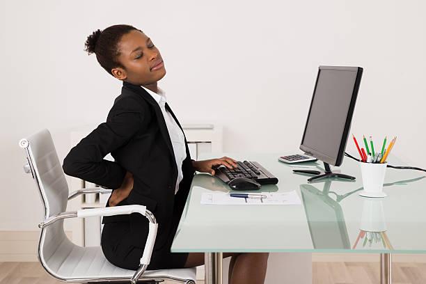 geschäftsfrau, die unter rückenschmerzen im büro - rückenschmerzen beim sitzen stock-fotos und bilder