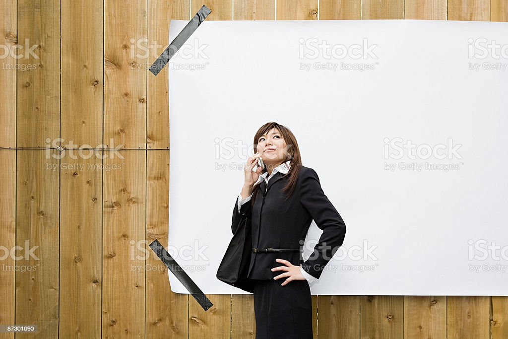 A businesswoman suing a cell phone royalty-free stock photo